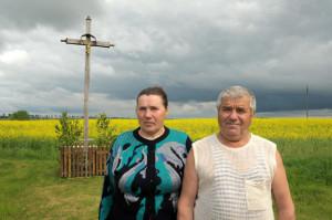 Сужэнства Міхаіл і Галіна Заяц каля крыжа пры ўездзе ў Даўгінава